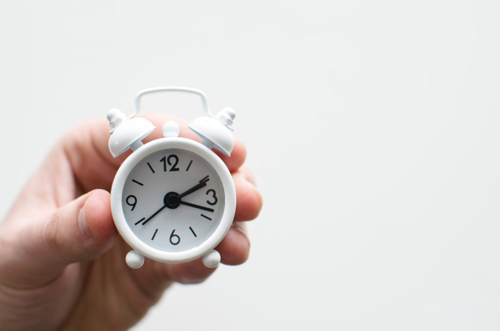 pessoa a segurar relógio pequeno branco