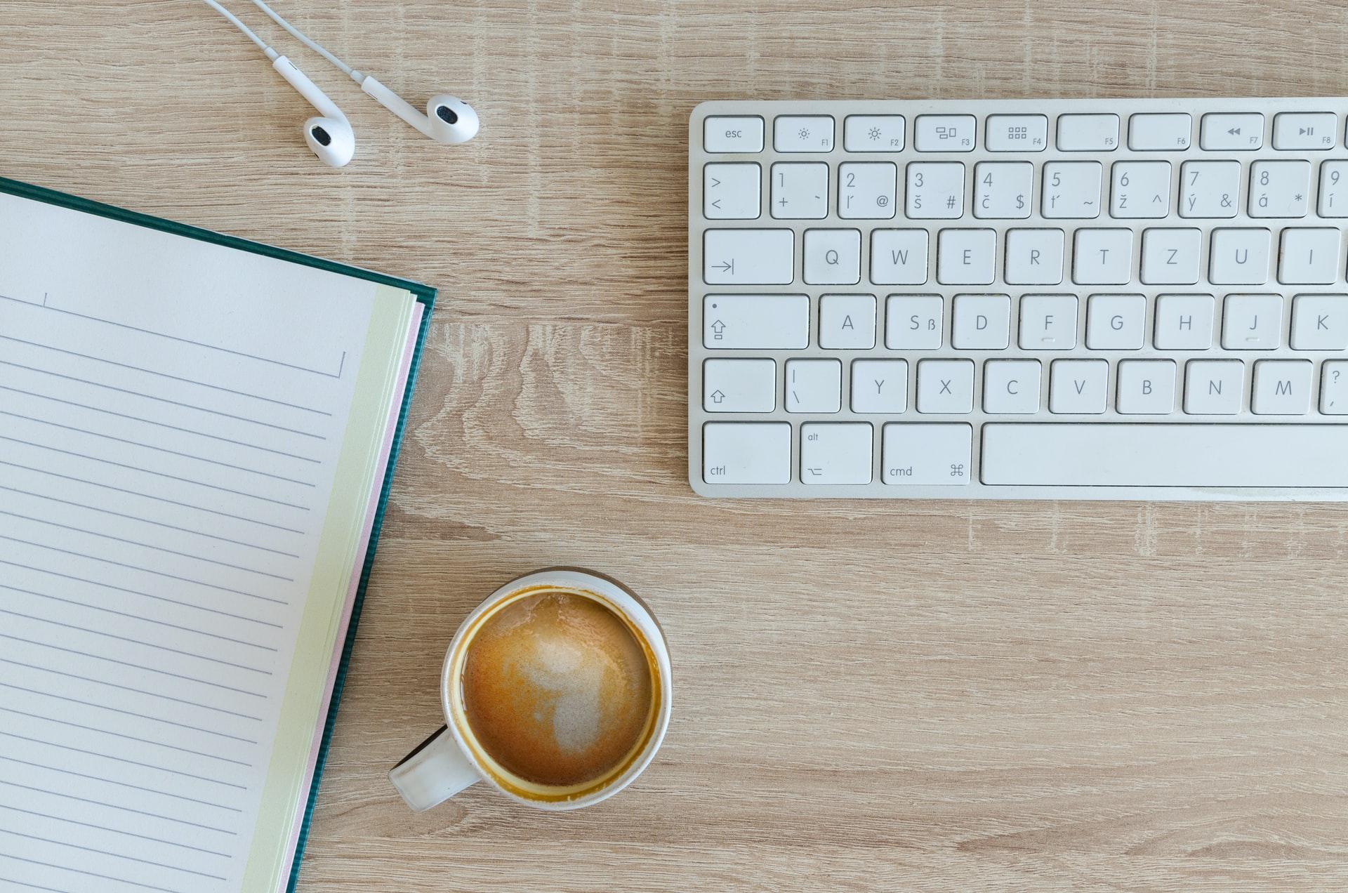chávena de café e teclado do computador