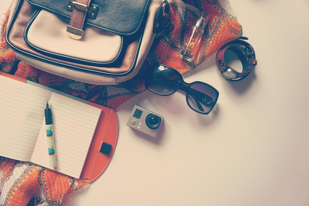 mala com bloco de notas oculos de sol e maquina fotografica