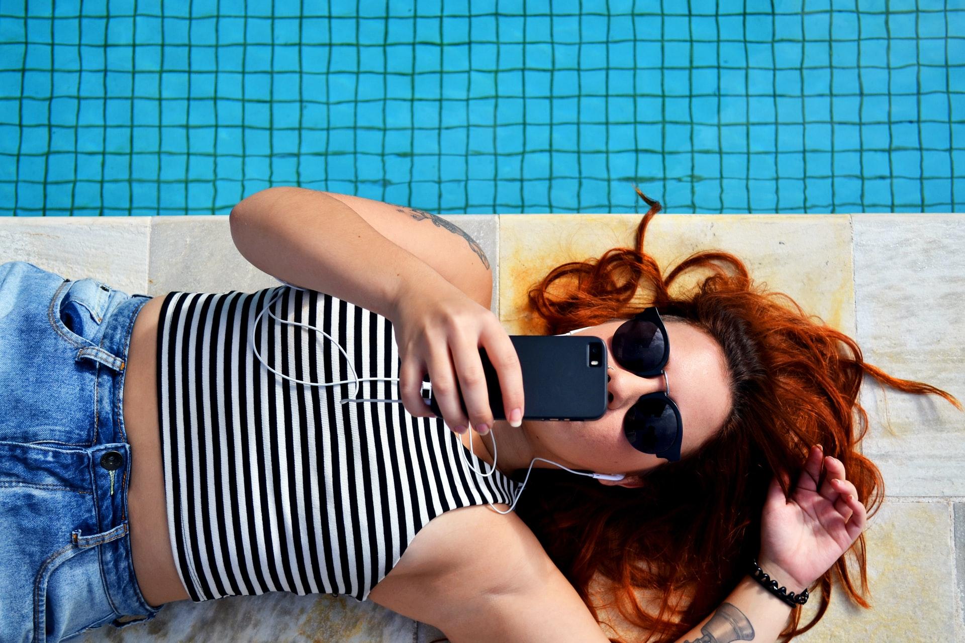 adolescente deitada à beira da piscina