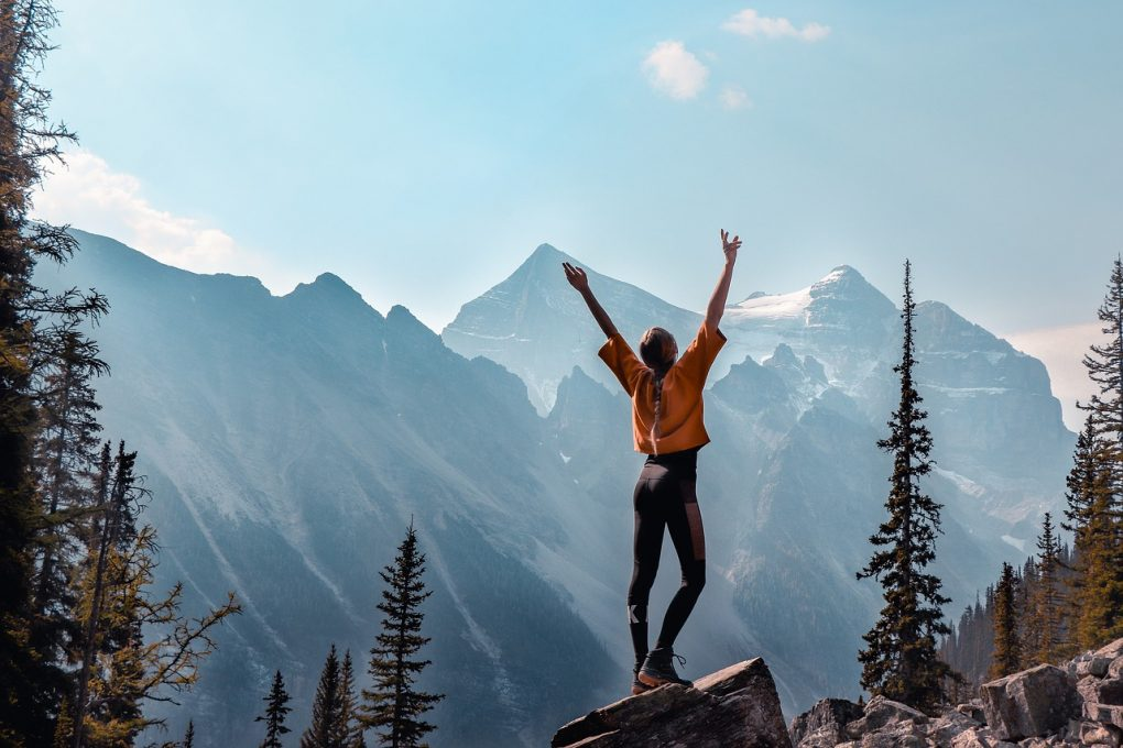 menina de braços abertos a olhar para uma montanha