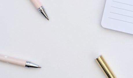 mesa branca com canetas e bloco