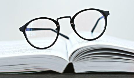 livro aberto com oculos por cima