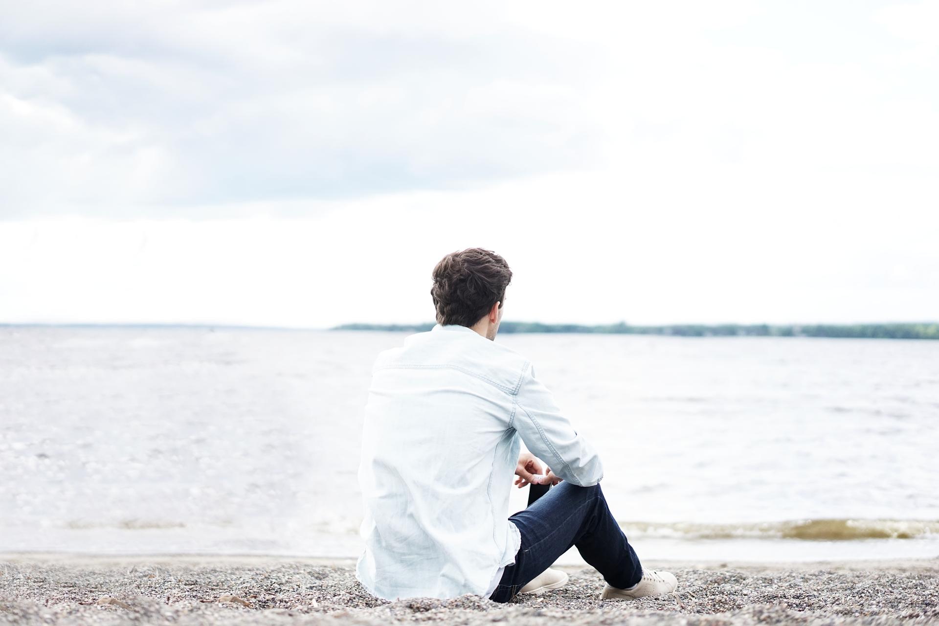 homem sozinho sentado na areia a olhar para o mar