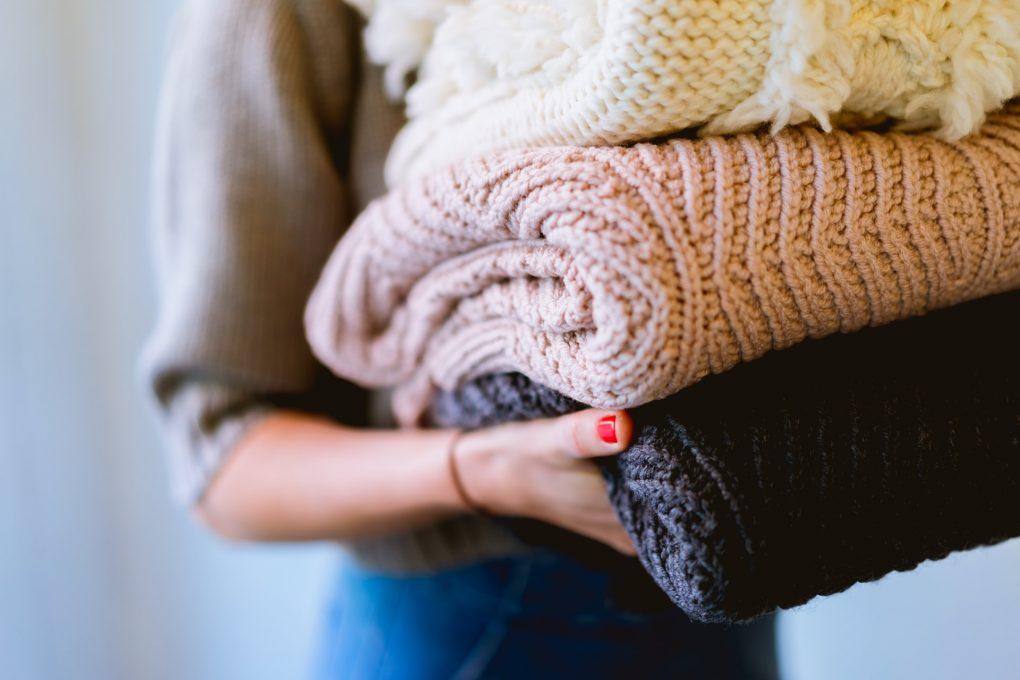 rapariga a pegar em camisolas de lã grossas