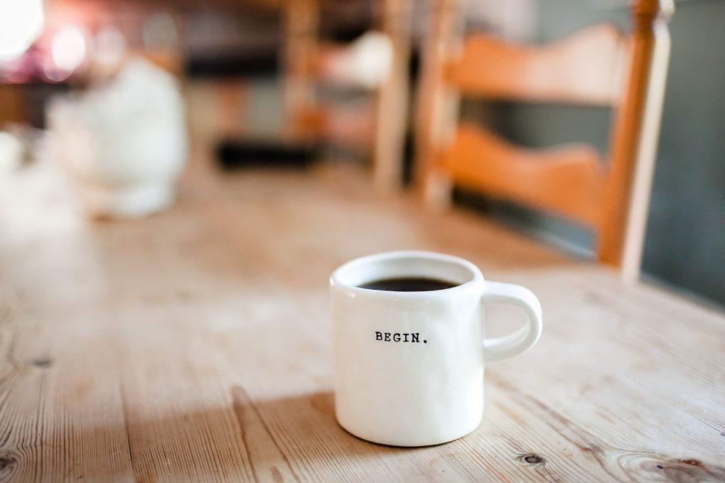 caneca branca com cafe com a palavra begin