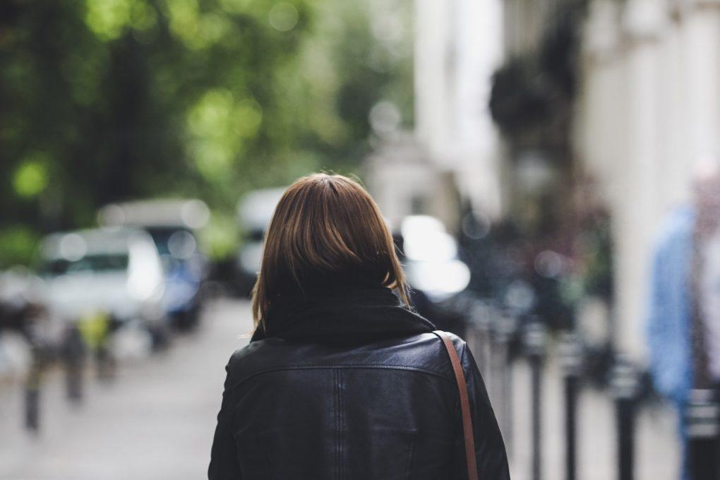 rapariga morena a andar na rua de costas