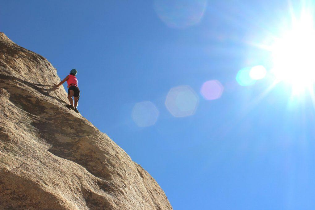 rapariga a escalar montanha num dia de sol