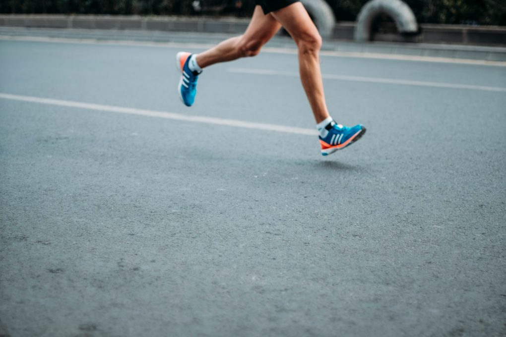 homem a correr com ténis azuis e laranjas