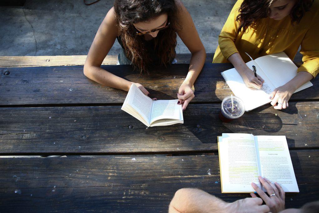 três raparigas a fazer multitasking na mesa de madeira