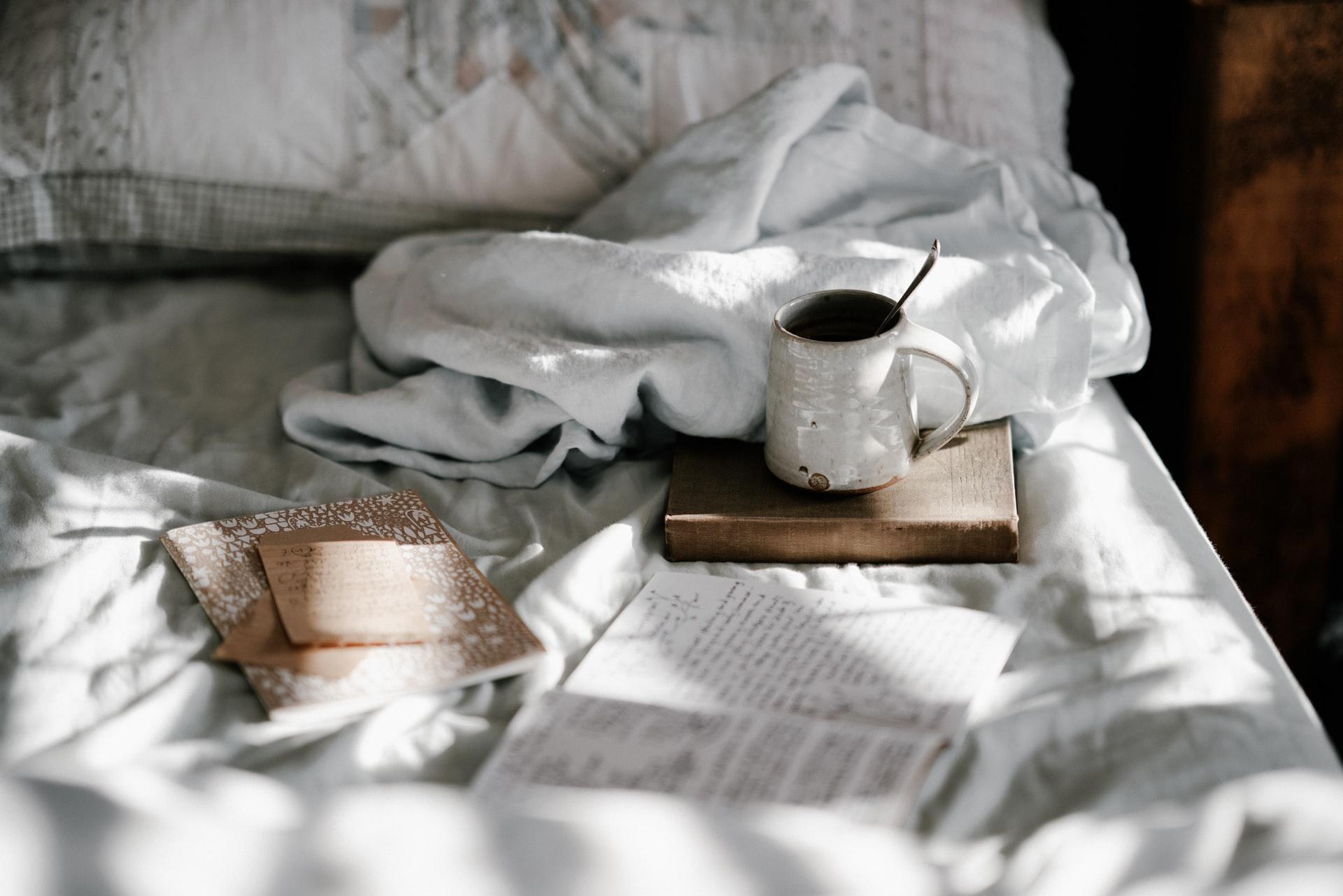 cama com tabuleiro e chávena de café