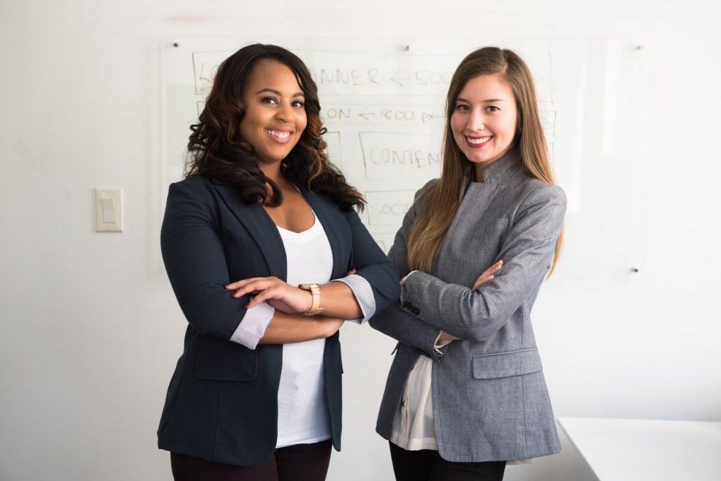 duas raparigas executivas a ter uma foto a cruzar os braços