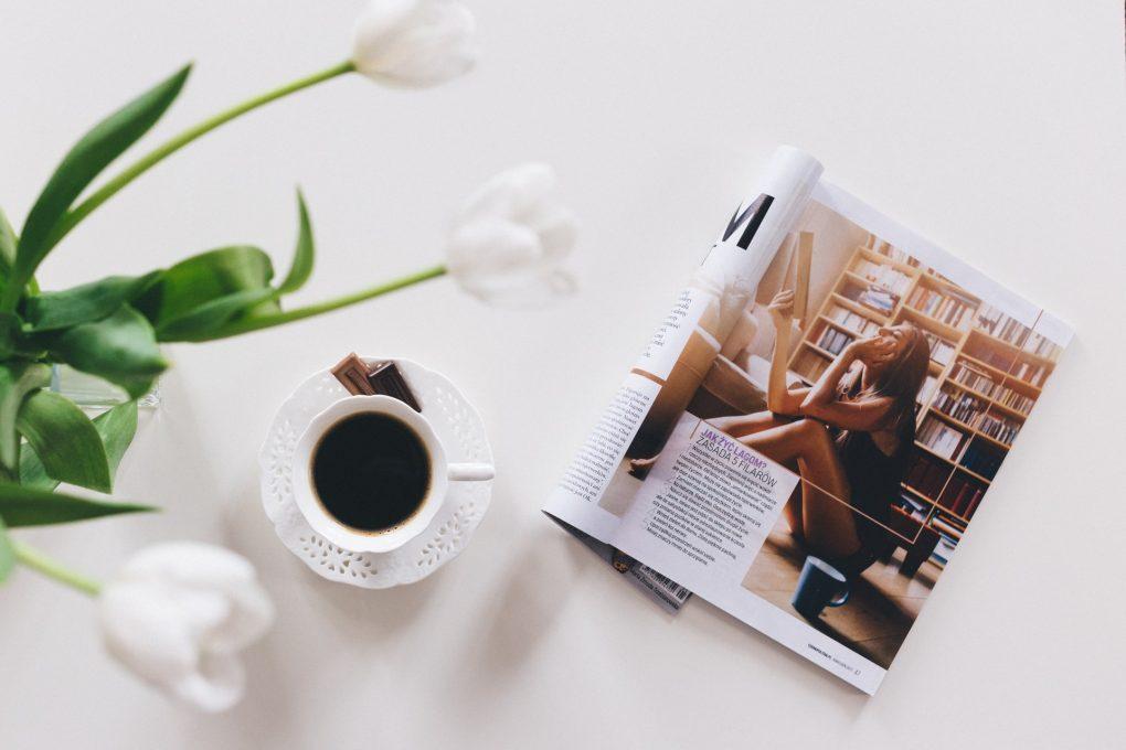 revista com imagem e uma chavena de cafe ao lado