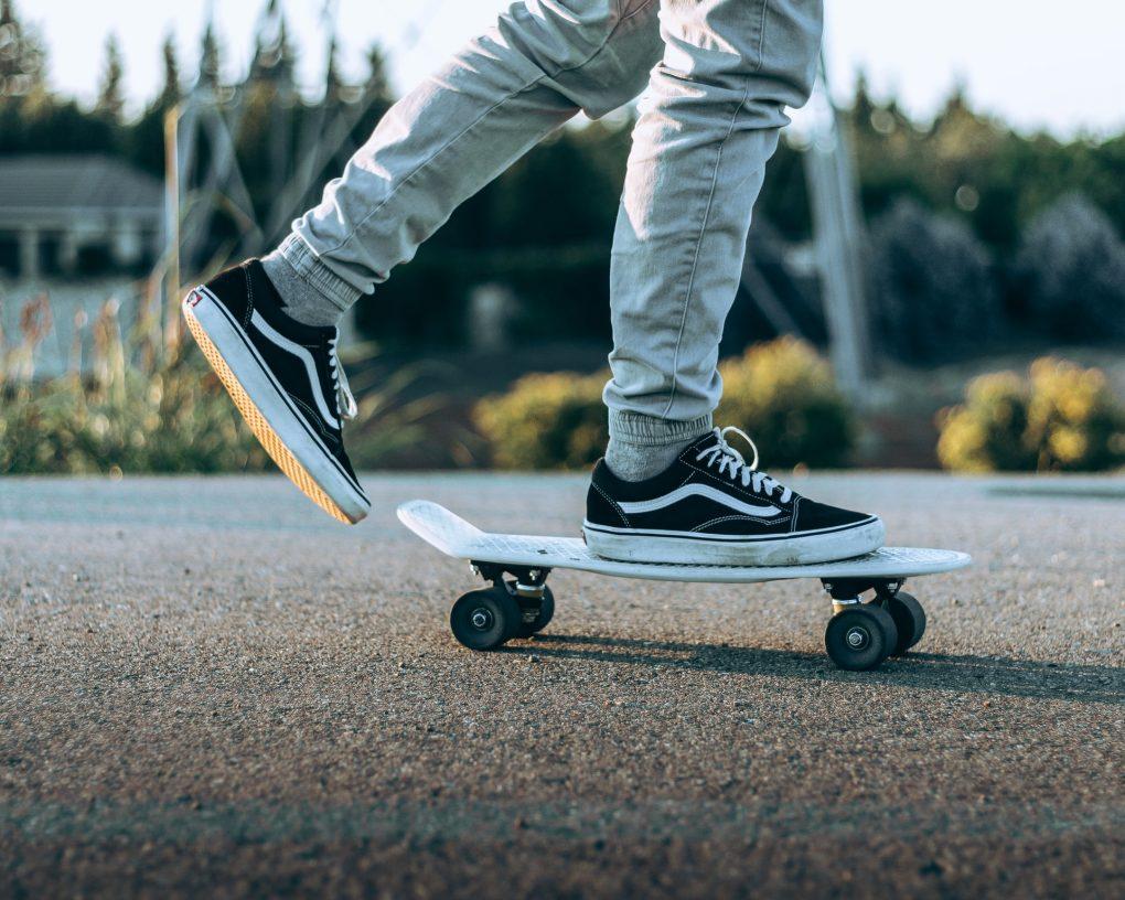 rapaz de 25 anos com vans pretos a andar de skate
