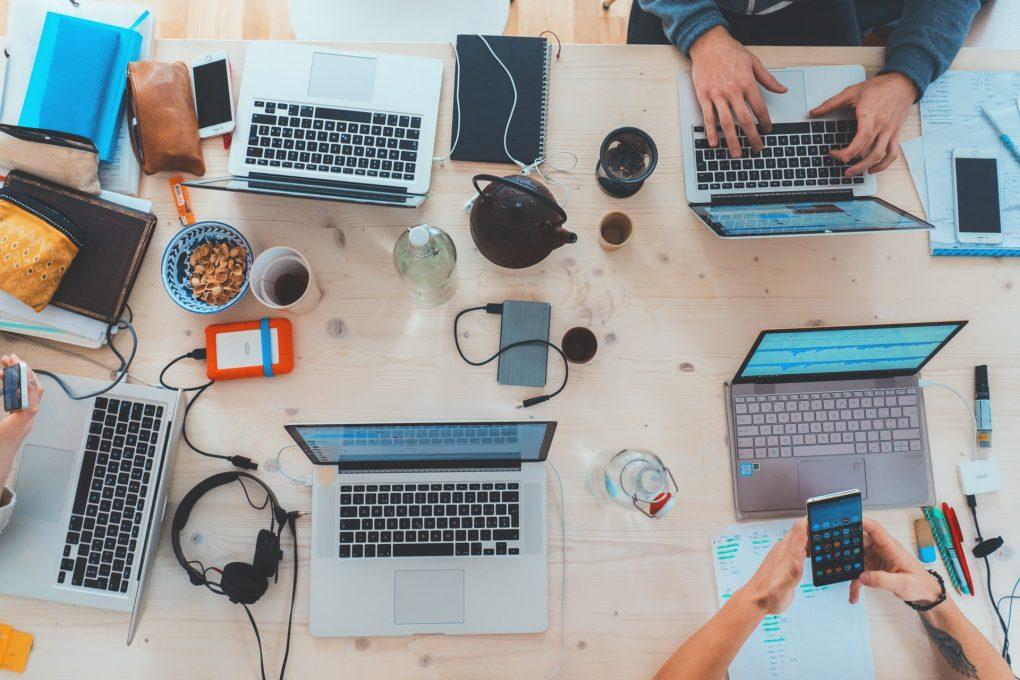 várias pessoas a trabalhar em computadores portáteis mac