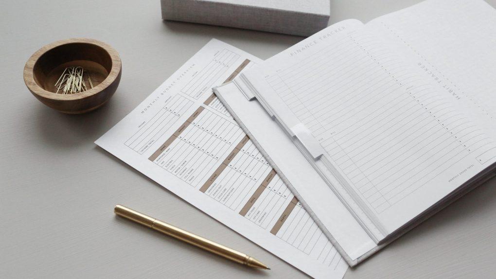 bloco de notas aberto com papel e caneta e uma concha com clips