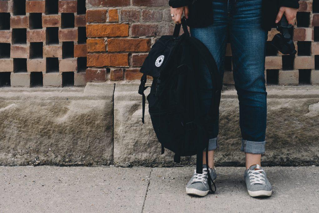 estudante a segurar uma mochila preta na mão
