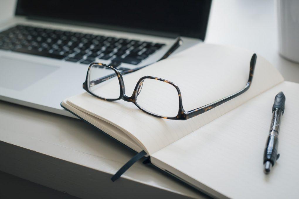 bloco de notas com uns óculos e uma caneta em cima