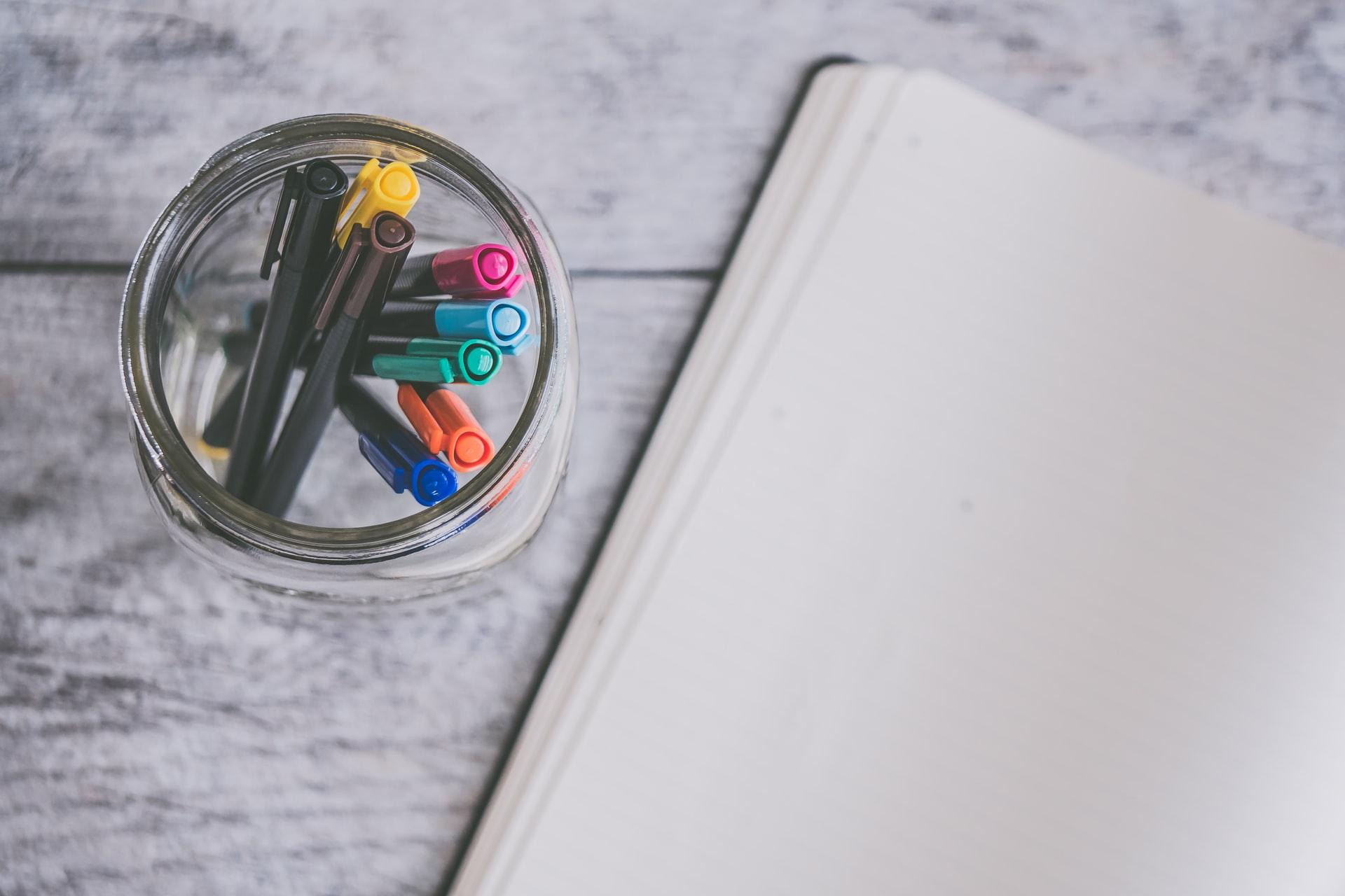 canetas coloridas e bloco de notas