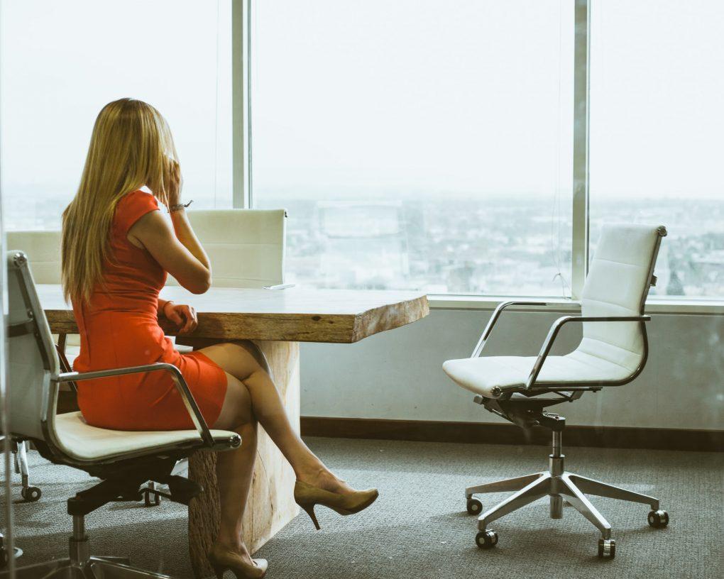 mulher de vestido laranja sentada numa mesa de reuniões