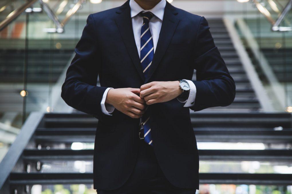 homem de fato e gravata a fechar um botão