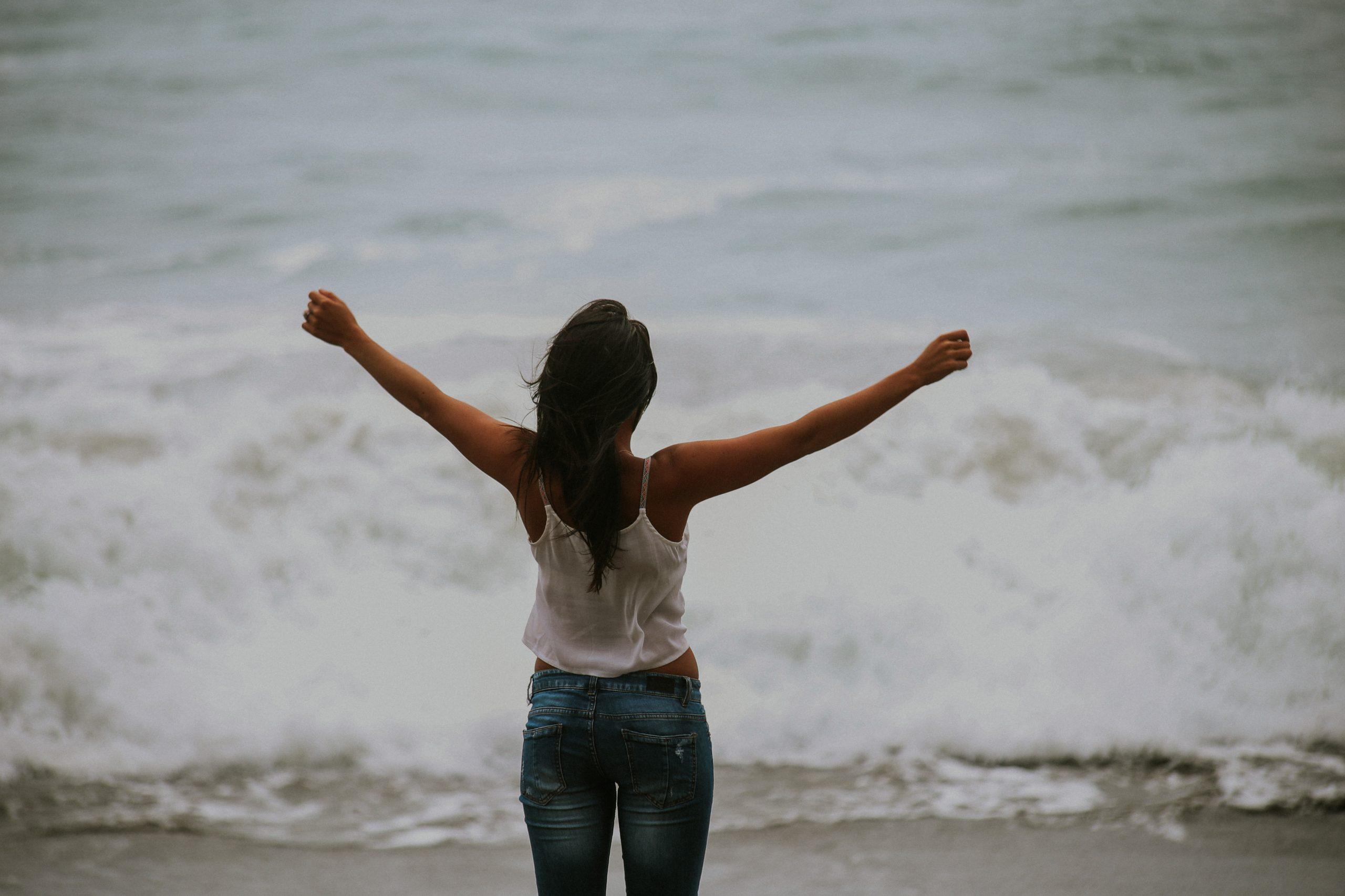 mulher com calças de ganga e top branco com os braços abertos a olhar para o mar