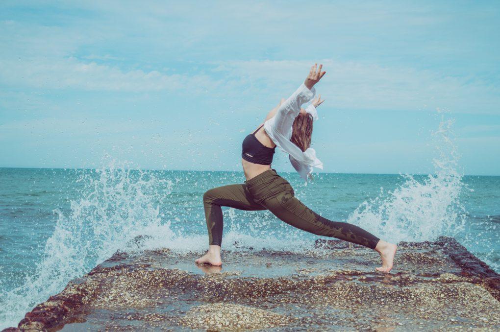 adaptabilidade rapariga a fazer yoga ao pé da água