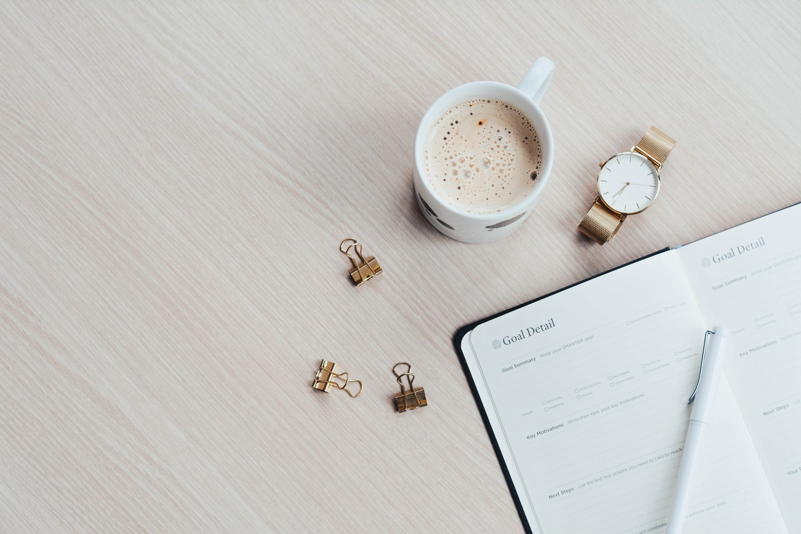 definir objetivos caderno aberto e chavena de cafe