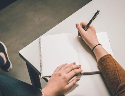 rapariga a escrever num blogo de notas para comunicar melhor no blog