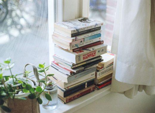 pilha de livros a janela de um quarto para ler mais