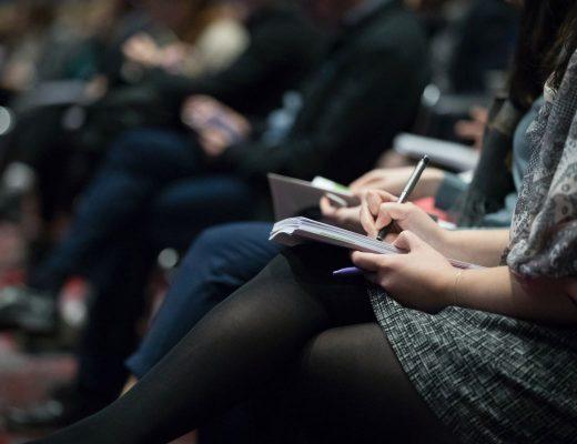 jornalistas numa conferencia a tirar notas