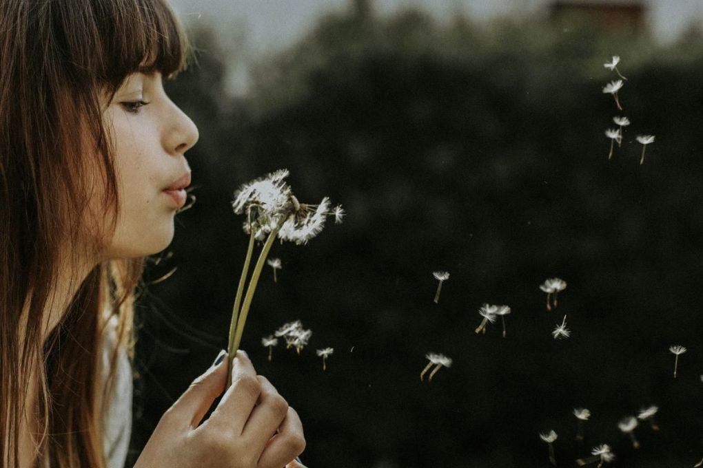 rapariga a respirar para uma flor para lidar com um mau dia