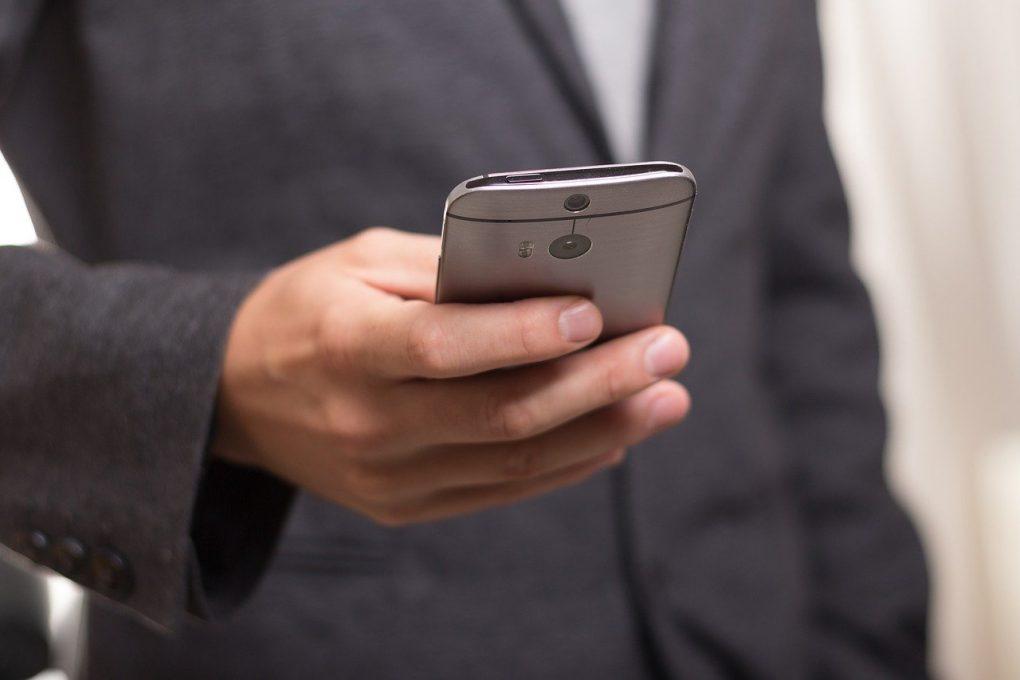 homem de fato a visitar uma newsletter no seu smartphone