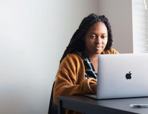 mulher negra a escrever como freelancer em casa