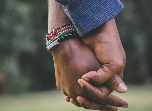 duas pessoas negras a dar aos maos