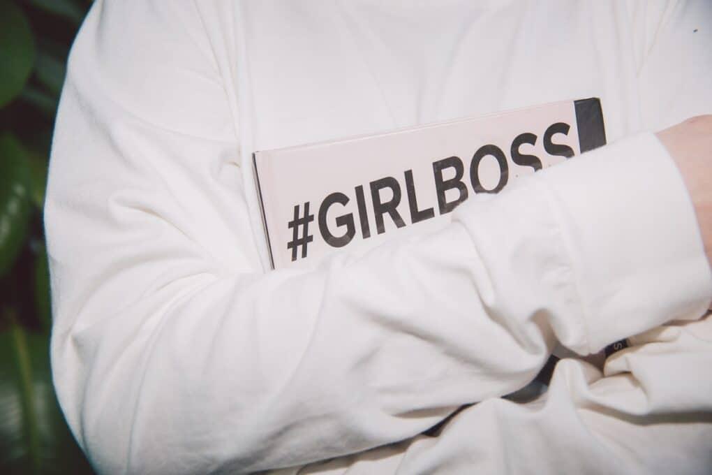 pessoa agarra jornal com hashtags girl boss
