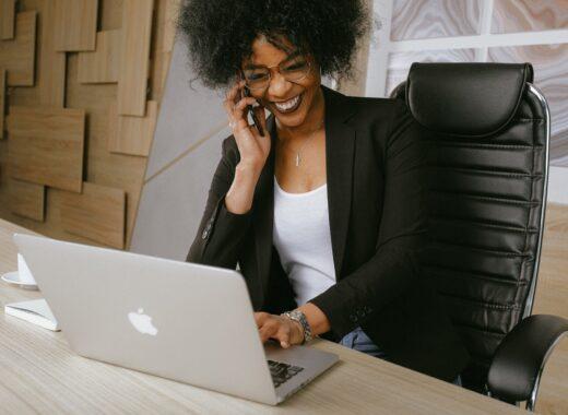 mulher negra sorridente a trabalhar no seu negócio digital