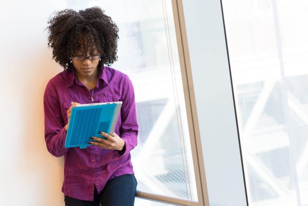 mulher negra profissional de comunicação a escrever no ipad