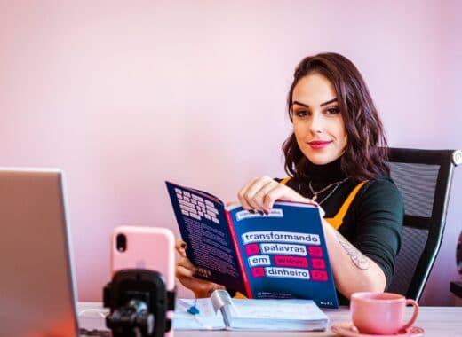 profissional de comunicação a ler um livro à secretária