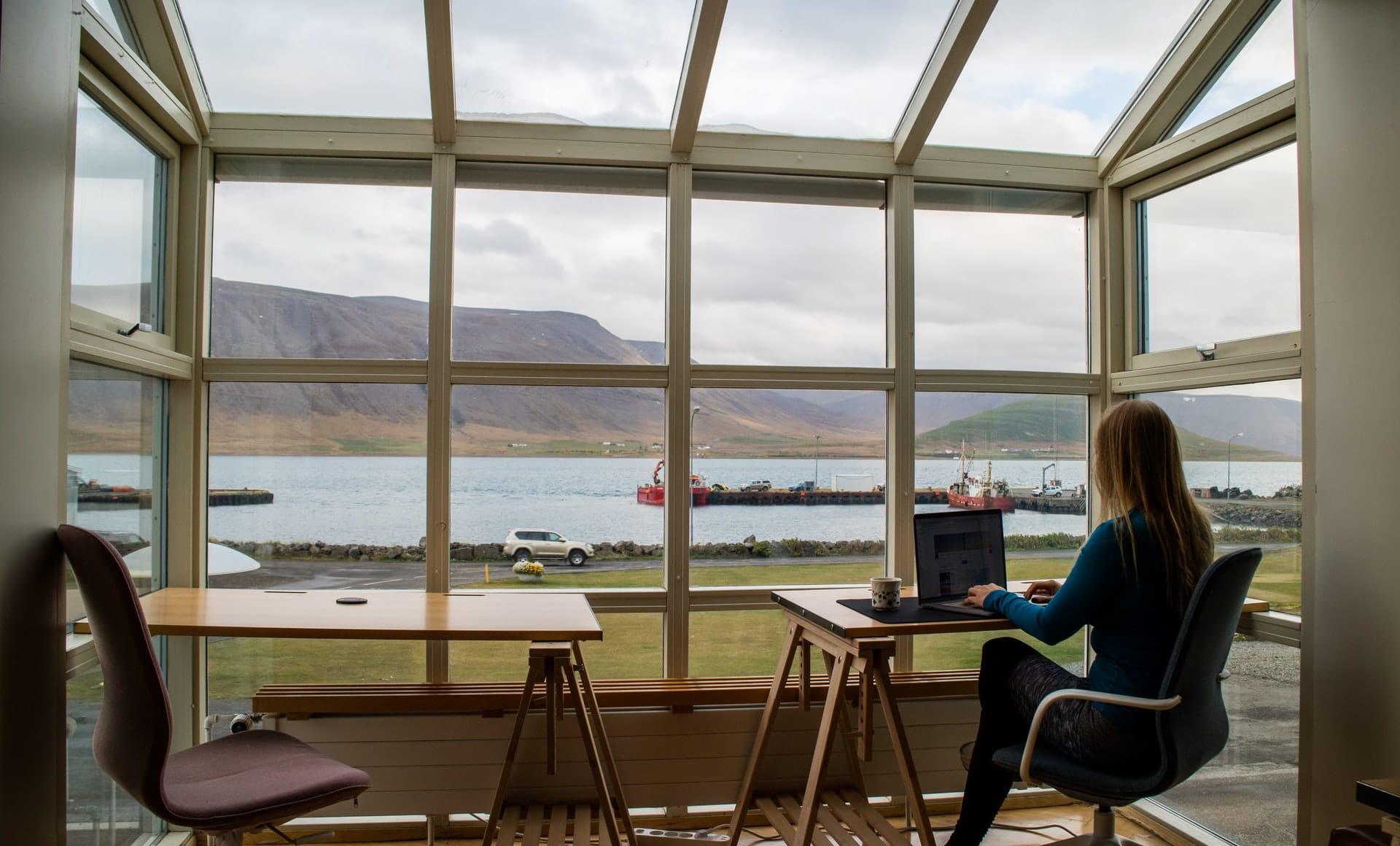 pessoa a trabalhar 4 dias por semana num escritório com vidros e a ver o rio